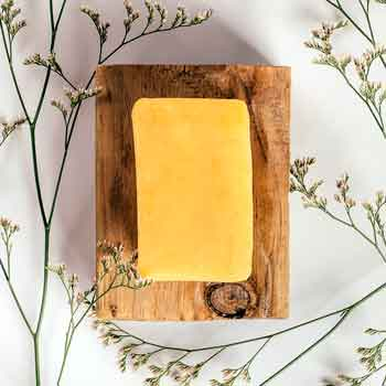 mango passion goat milk soap on wood with flowers