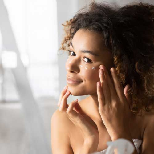 Woman applying goat milk under eye cream